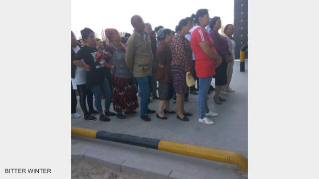 I familiari dei detenuti che assistono al processo pubblico si allineano fuori dal campo in attesa di essere convocati