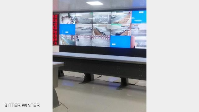 Lo schermo gigante nella stanza di sorveglianza del campo di rieducazione