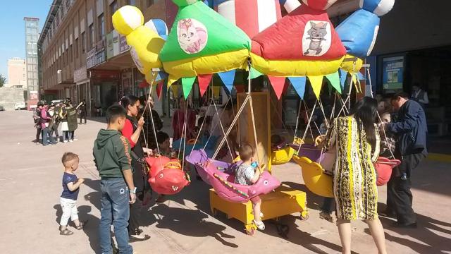Immagini contrastanti dallo Xinjiang: bambini che giocano sulla giostra e sullo sfondo la «milizia territoriale» del mercato di Hotan che si sta addestrando