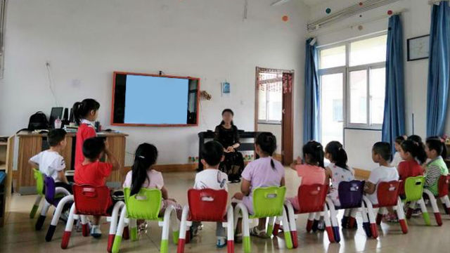 Un insegnante dell'asilo in classe sta parlando ai bambini